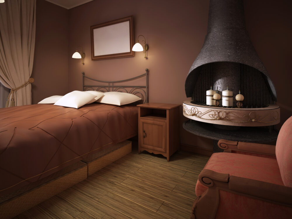 A dark brown bedroom in rustic style with a fireplace with a wrought-iron bed.