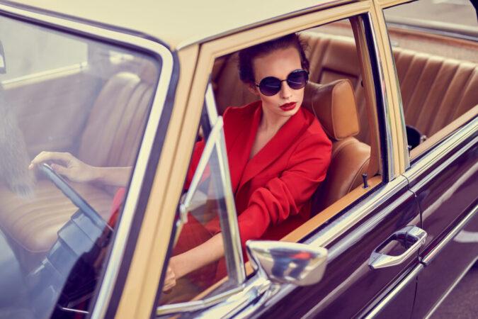 Beautiful young woman in retro car