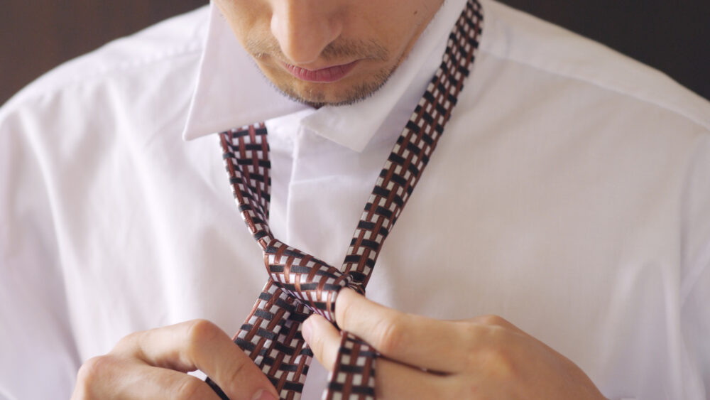 Man in white shirt tying a tie. Close-up