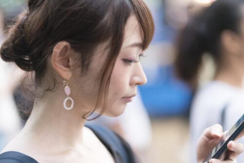 pixta_56724086_M 渋谷スクランブル交差点 スマホを操作する女性