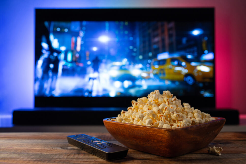 A wooden bowl of popcorn and remote control in the background the TV works. Evening cozy watching a movie or TV series at home. 映画・ドラマ鑑賞