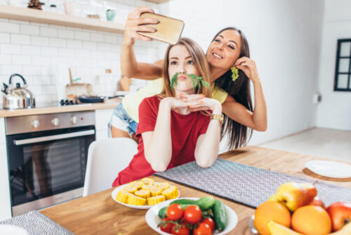 Women preparing food playing with vegetables in kitchen having fun and taking selfie