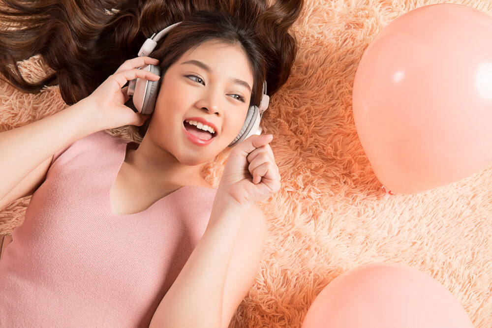 Young Asian woman listening and singing happily.