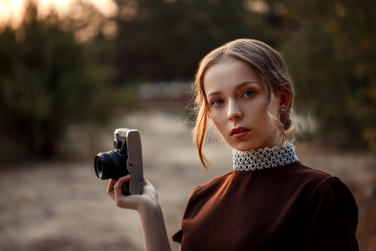 close-up portrait of a young beautiful girl in a brown dress in a retro style with a vintage camera in her hands on an abandoned road.