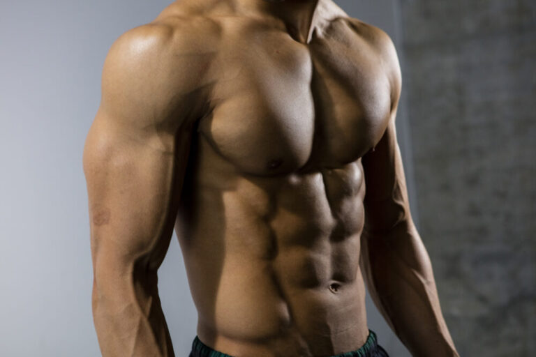 A fitness model's chiseled torso. Close up. Side view.