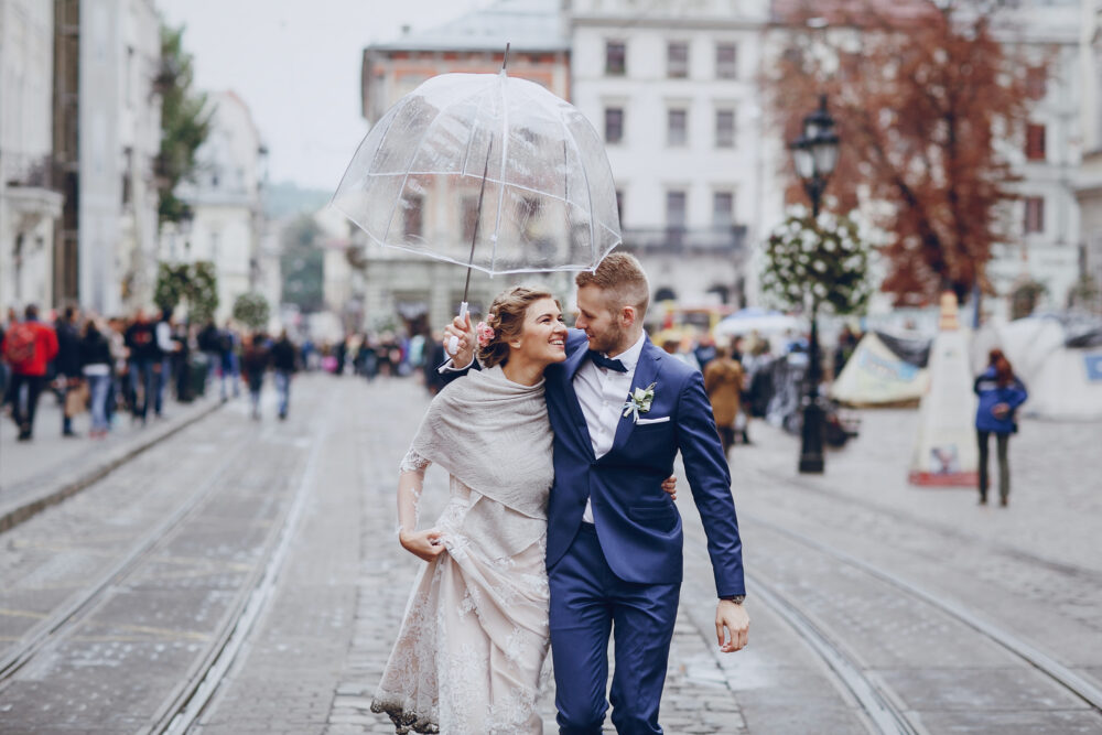 beautiful and elegant blonde bride in a long white dress with her handsome bride in a blue suit wallkig in a raining city with umbrella