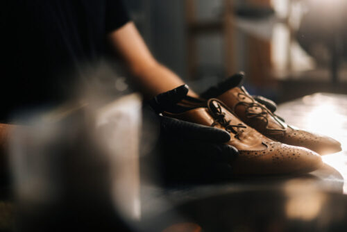 Close-up side view of hands of shoemaker shoemaker in black gloves holding old worn light brown leather shoes on table to be repaired in dark craft shoe shop. Concept of cobbler artisan work.