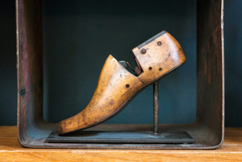 Old vintage wooden shoe form for production and repair of handmade shoes by a cobbler displayed on a stand on a shelf in side view