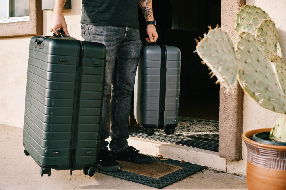 スーツケース(キャリーバッグ)を持つ男性の画像