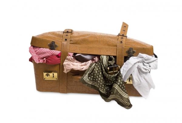 荷物でいっぱいになっているスーツケースの画像