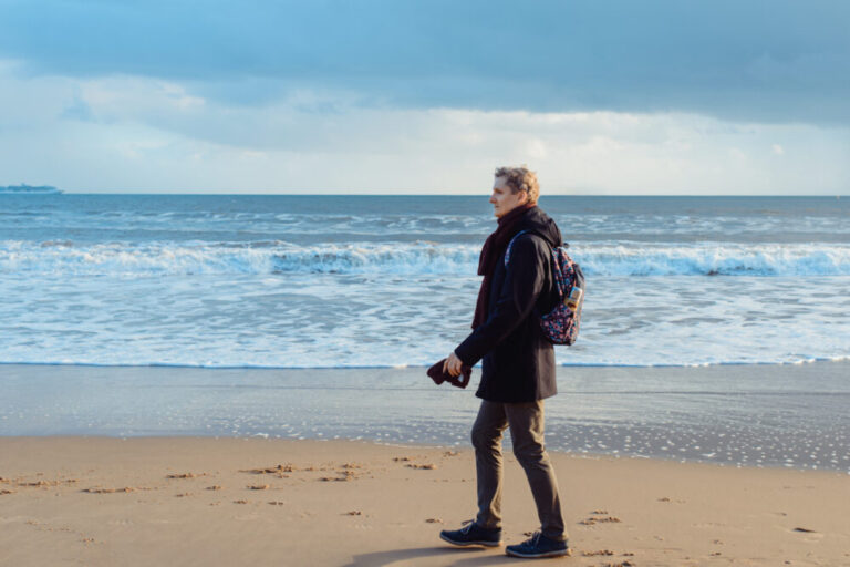 A young man in warm clothes with backpack walking on winter seaside and enjoying the moment. Relax during a walk on the coast. Simple pleasures. Travel in autumn, winter. Selective focus. copy space.