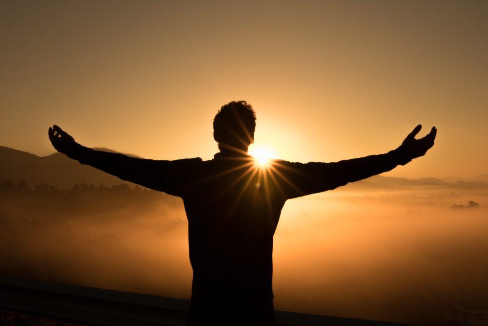 夕陽を仰ぐ男性の画像